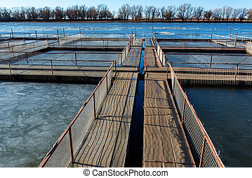 Winter view of fish farm for brooding sturgeons with natural pools in river