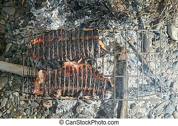 Fish fillets grilling on hot open fire coals - Fish fillets...