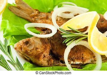 Fish fried, a crucian with a lemon, rosemary and olive oil