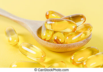 Fish oil capsules in wooden spoon.