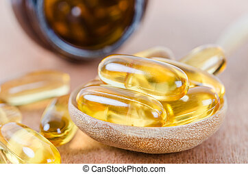 Fish oil capsules in wooden spoon with bottle.