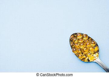 Fish oil capsules with omega 3 and vitamin D blue texture, healthy diet concept, selective focus.