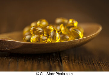 Fish oil capsules with omega 3 and vitamin D in a wooden spoon on wooden texture, healthy diet concept.