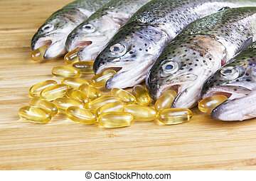 Fish Oil Time - Fish capsules with freshly caught trout on ...
