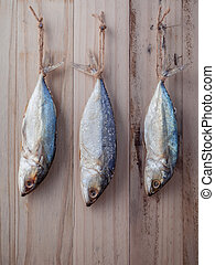 Fish preservation by drying . Sardine salted hanging on old wooden background .
