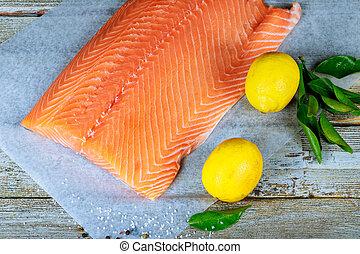 Fish Raw salmon fillet pepper salt dill lemon on wooden table.