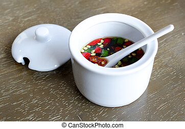 Fish Sauce Thailand in a white cup .