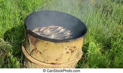 fish smoking rusty barrel