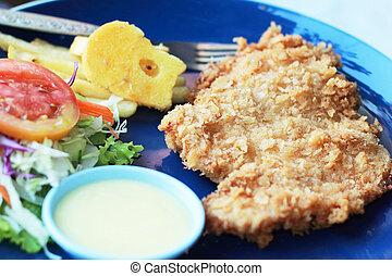 Fish steak with vegetable salad on plate.