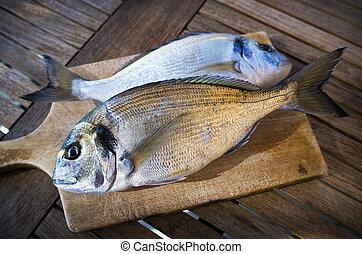 Fish - Delicious fresh sea bream fish on wooden kitchen...