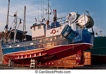 Fish trawler on land during off peak season, ship goes ...