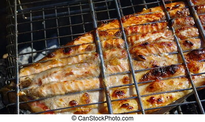 Fish trout on the grill. Summer barbecue concept. Close up...