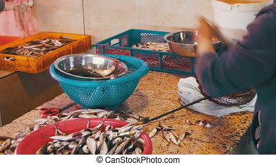 Fish Vendor Scaling and Cutting Fish in Market Stall. Manual...