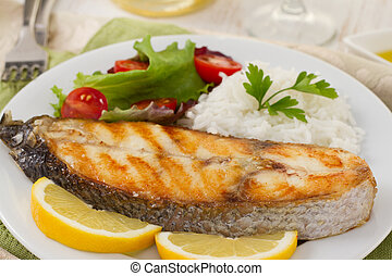 fish with boiled rice and salad on the plate