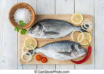 fish with spices on a wooden background