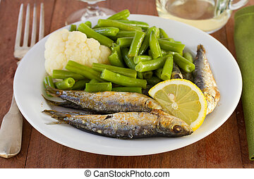 fish with vegetables on the white plate
