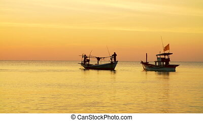 Fisher boats at sunset on the horizon