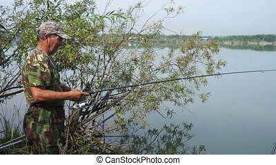 Fisher - Fishing on the lake fisherman throws a spinning