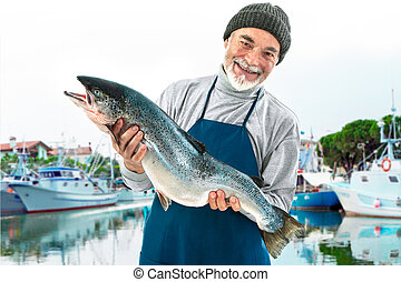 Fisher holding a big atlantic salmon fish in the fishing ...