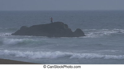 Fisher Standing Alone On A Big Rock, Lots Of Wavebreaker, native Version