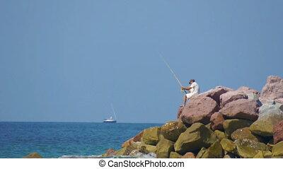 Fisherman - A man sitting on the oceanside, fishing.