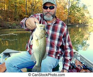 fisherman holding a large mouth bass closeup