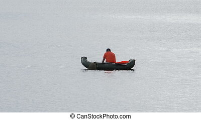 Fisherman and boat on lake waves. Shot in RAW, wide dynamic range