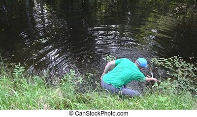 Fisherman angler man clean private lake water from plants and rubbish.