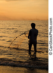 Fisherman at beach with fishing net during sunset