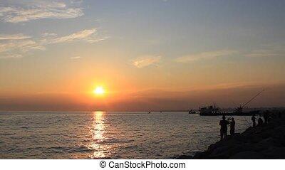 Fisherman at sunset - Fisherman silhouettes against sunset