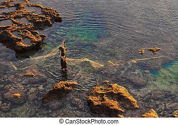 Fisherman at the sea coast with fishing net