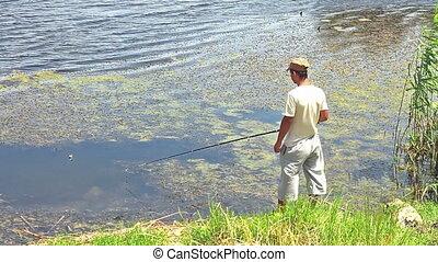 Fisherman - Back view of fisherman catching fish at pond