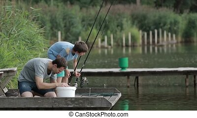 Fisherman baiting hook on fishing rod at lake - Angler...