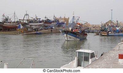 fisherman boats foing to sea, essaouira, morocco
