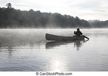 Fisherman Canoeing on a Misty Lake - Ontario, Canada