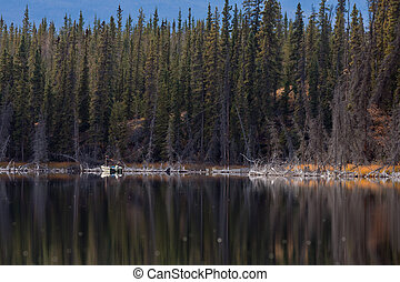 Fisherman casting lure on calm Yukon lake in fall