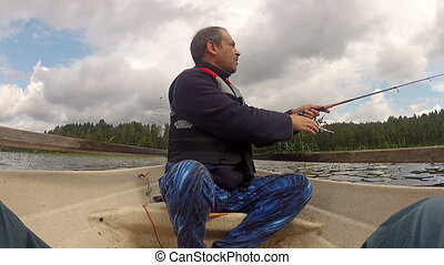 Fisherman catches a fish on boat