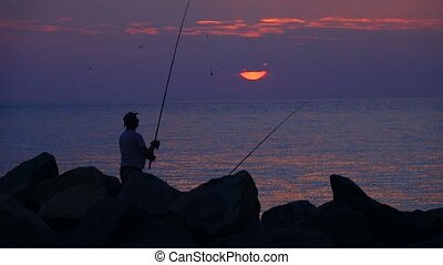 fisherman catches fish in the background the sun rises over...
