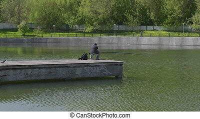 Fisherman catches fish in the lake with a fishing rod....