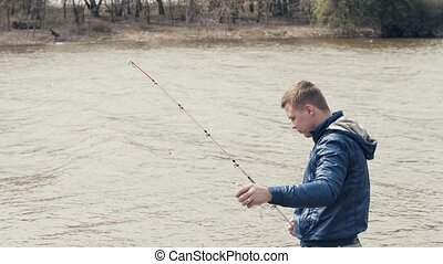 Fisherman catching fish. Angler taking caught fish from hook...