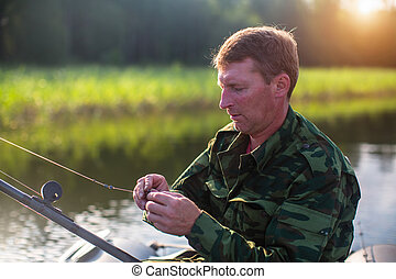 Fisherman catching fish on the lake from boat.