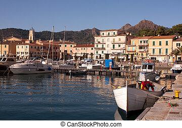 Travel, Italy - Old fisherman cleaning fishnets in his boat - Porto Azzurro, Eba Island, Italy.