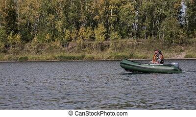 Fisherman - fisherman floats on a motorboat