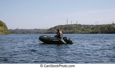 Fisherman - fisherman sitting in the boat fishing spinning...