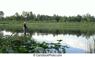 fisherman fishing in a calm river in the morning. Man in...