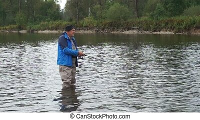 fisherman - Fishing on the mountain river with fast current
