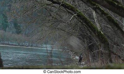 Fisherman fishing on the river bank