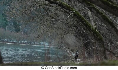 Fisherman fishing on the river bank - A fisherman fishing on...