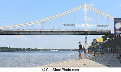 Fisherman fishing on the waterfront near the bridge