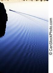 fisherman floats on a motor boat, river, lake, sea, sunset, sunrise..